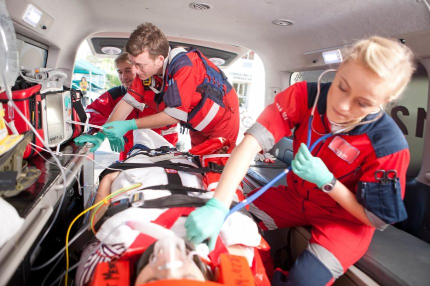Paramedics helping patient in ambulance
