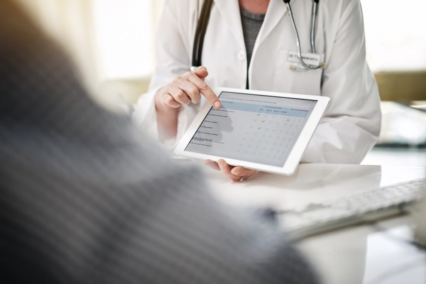 doctor holding up tablet to patient