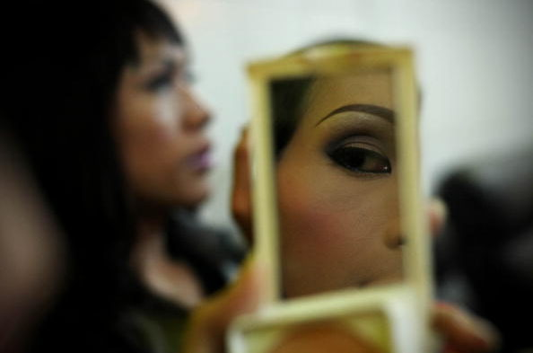 Transgender woman looking in a mirror