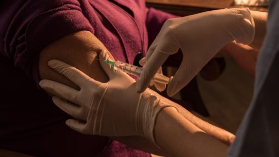 Woman getting vaccine in her arm
