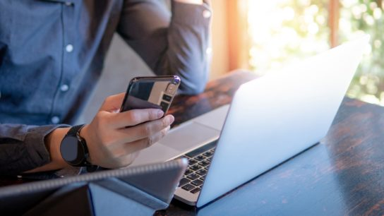 man on mobile device and laptop