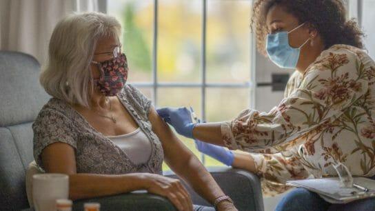 At home care nurse vaccinates an elderly woman.