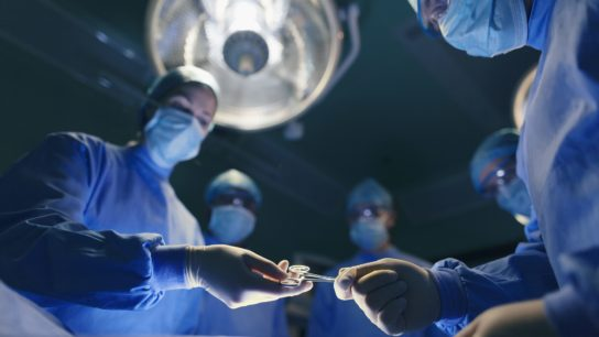 A room of surgeons operating on a patient.