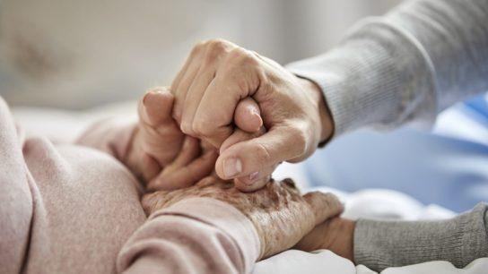 caregiver holding hands of older adult woman