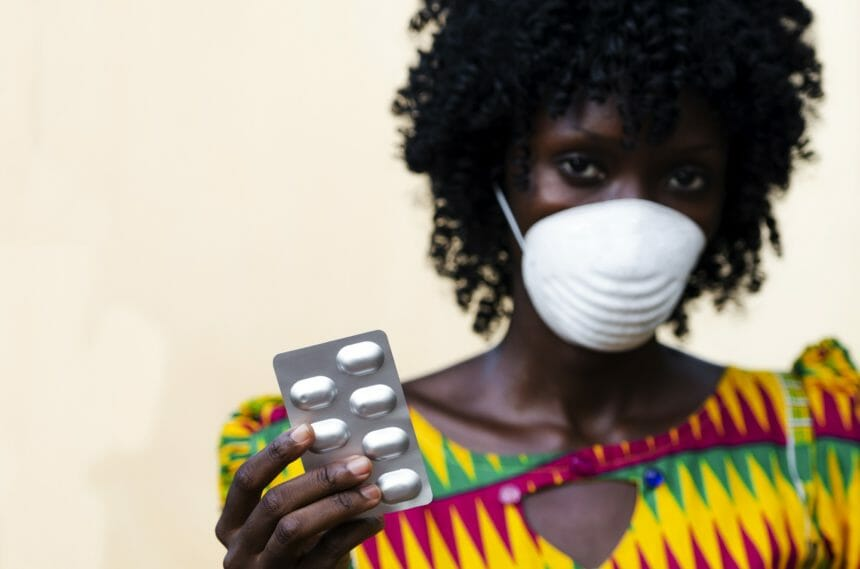 african woman holding pill sleeves